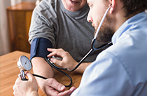 A man has his blood pressure measurement taken by a medical professional