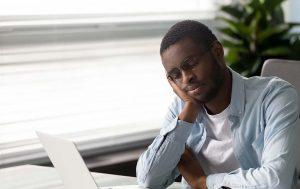 Man falling asleep at desk due to sleep apnea