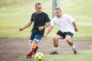 Two men playing soccer after getting energy levels back from testosterone replacement therapy