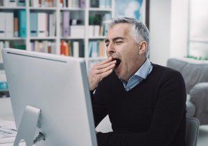 man yawning at work due to sleep apnea